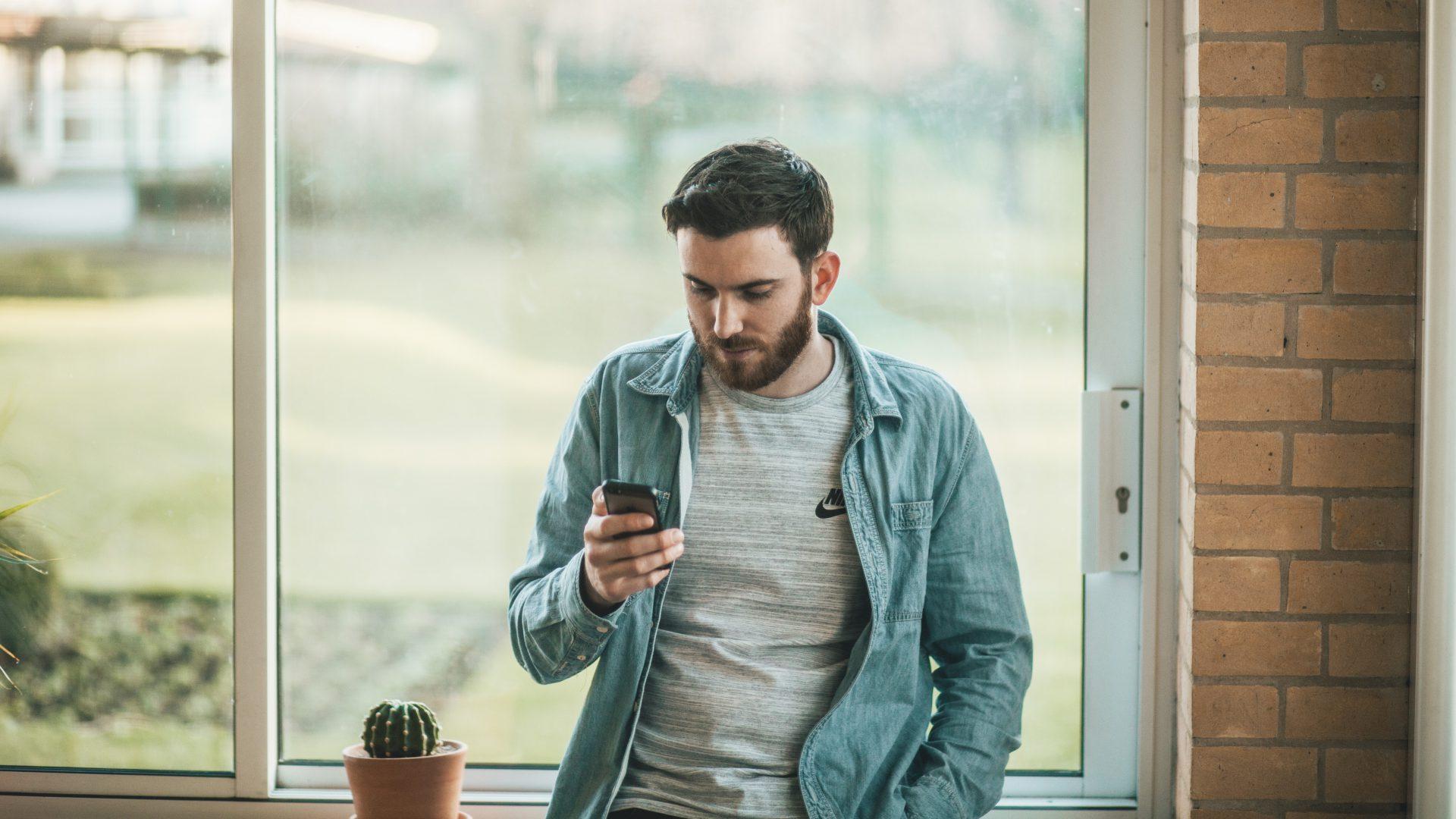 zittende man kijkt naar zijn smartphone